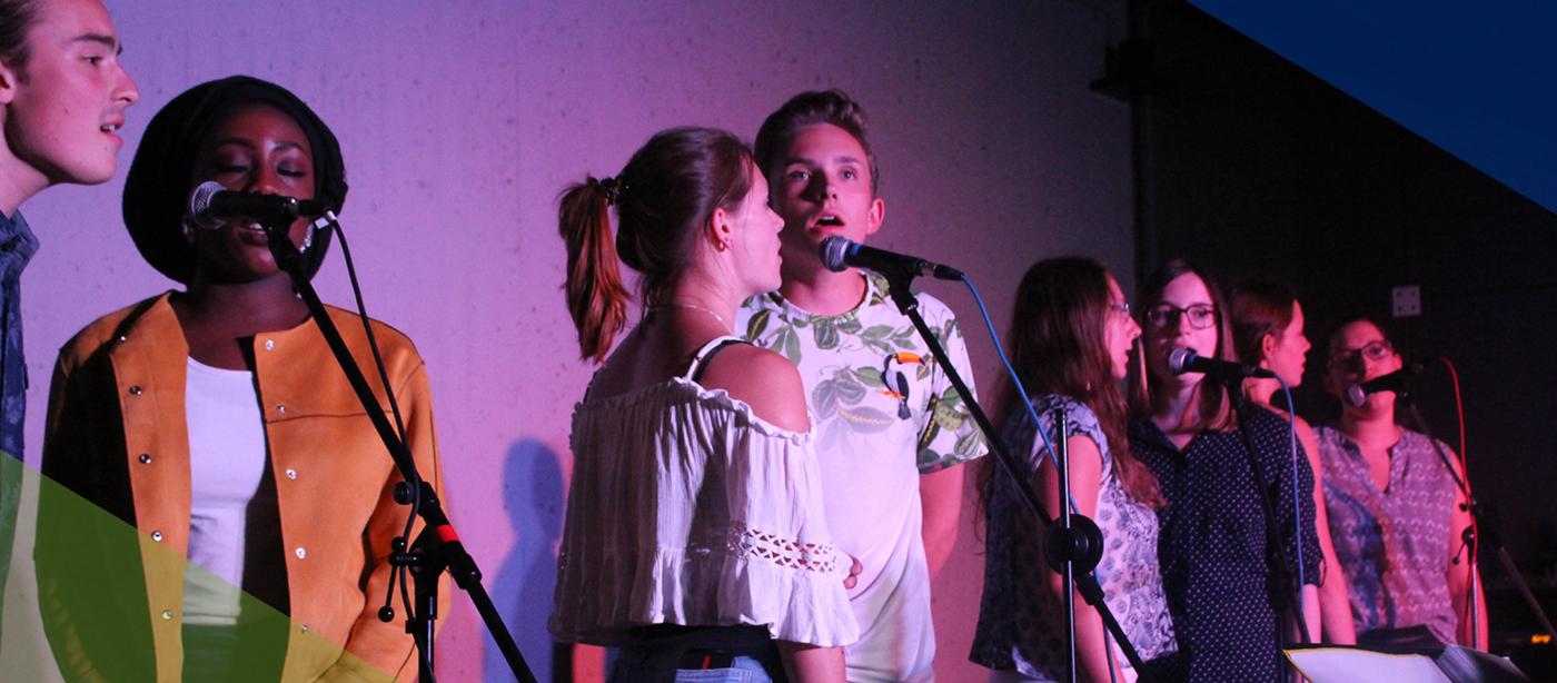 Singende Menschen im FSJ Ganztagsschule, die in Zweiergruppen auf einer Bühne singen