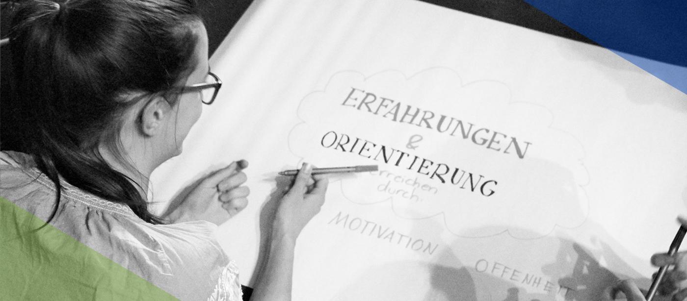 """Freiwilligendienst RLP: Freiwillige malt ein Plakat auf dem """"Erfahrungen & Orientierung erreichen durch Motivation, Offenheit"""" steht"""